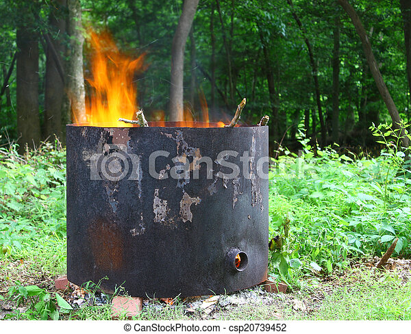 An old home made metal burn ring for burning tree stumps that have been left in the ground after the tree has been cut down - csp20739452