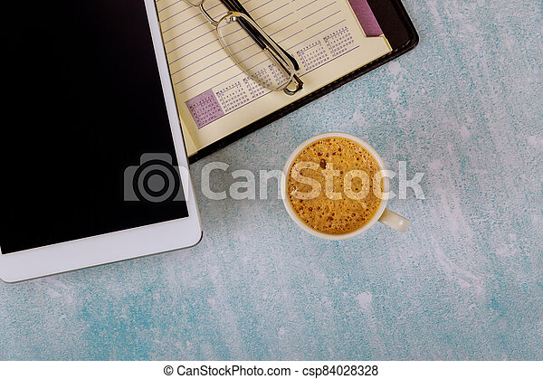 An open weekly notebook and digital tablet eyeglasses on the table a cup of coffee. - csp84028328