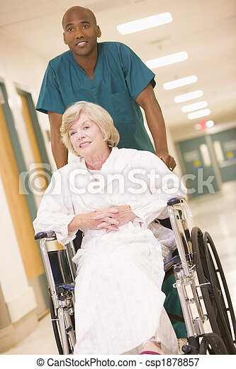 An Orderly Pushing A Senior Woman In A Wheelchair Down A Picture