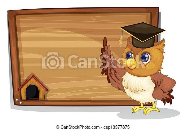 An owl wearing a graduation cap beside a wooden board - csp13377875