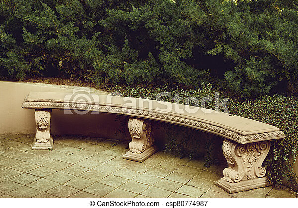 ancient empty marble bench under a green plant in the park - csp80774987