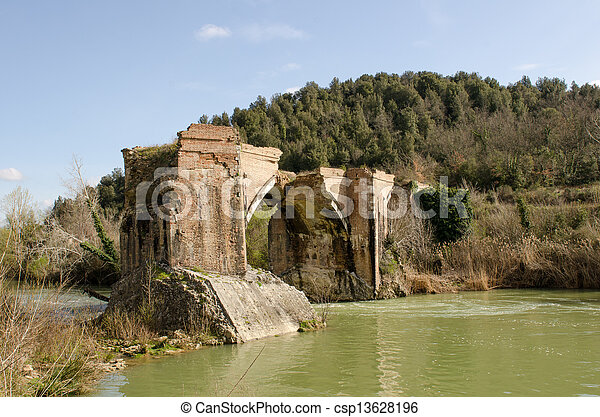 Ancient Medieval Bridge over a Creek in the Tuscany Countryside - csp13628196