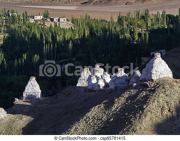 Ancient white Buddhist stupas on the ridge of a high hill in the Ladakh valley, the evening rays of the sun illuminate the stupas and long shadows stretch from the stupas along the mountain slope, the Himalayas, Northern India. - csp65781415