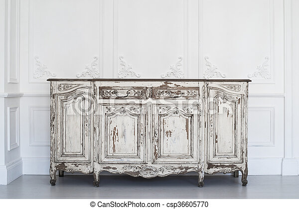 Ancient white commode bureau with paint peeled off on luxury wall