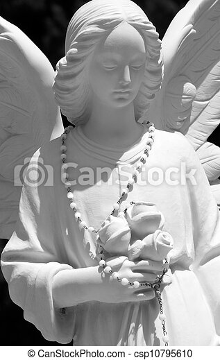 angel sculpture with chaplet and roses  - csp10795610