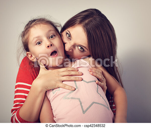Angry emotional young mother wanting to bite her naughty capricious daughte - csp42348532