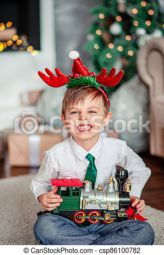 Angry upset little boy with a gift, toy train, under the Christmas tree on New Year's morning. Time to fulfill wishes. - csp86100782