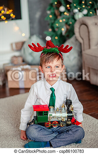 Angry upset little boy with a gift, toy train, under the Christmas tree on New Year's morning. Time to fulfill wishes. - csp86100783