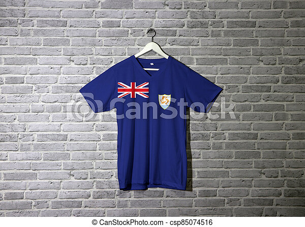 Anguilla flag on shirt and hanging on the wall with brick pattern wallpaper. - csp85074516