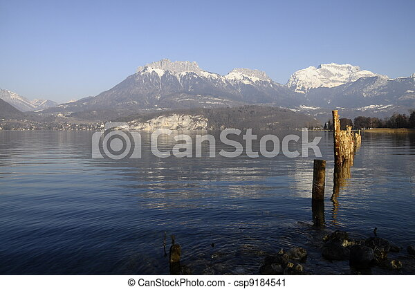 Annecy lake and mountains of Tournette and Forclaz with wooden poles in foreground - csp9184541