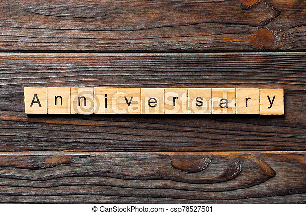 anniversary word written on wood block. anniversary text on wooden table for your desing, concept - csp78527501