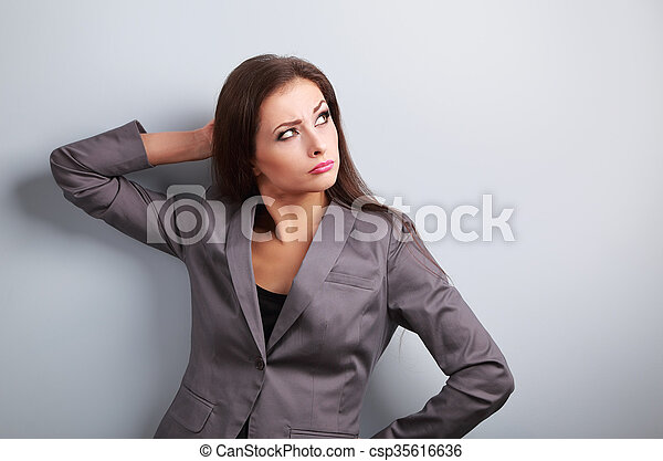 Annoyed concentration business woman in suit looking up on blue background - csp35616636