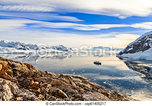 Antarctic mountain landscape with cruise ship standing still in - csp61405217