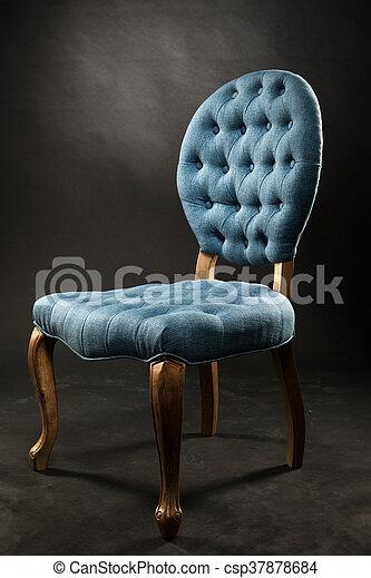 Una antigua silla de terciopelo azul cerca de una habitación oscura - csp37878684