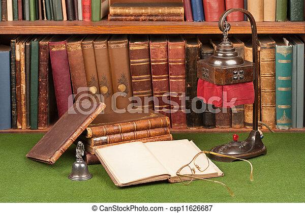 Libros antiguos de cuero, lámparas y lentes de lectura en manchas verdes. - csp11626687