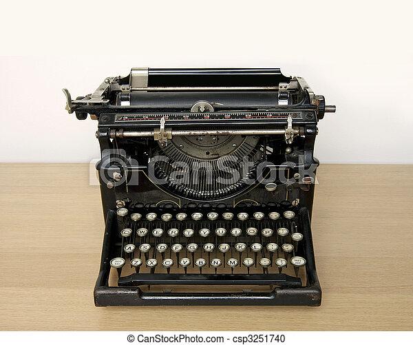Una máquina de escribir antigua en un escritorio de madera - csp3251740