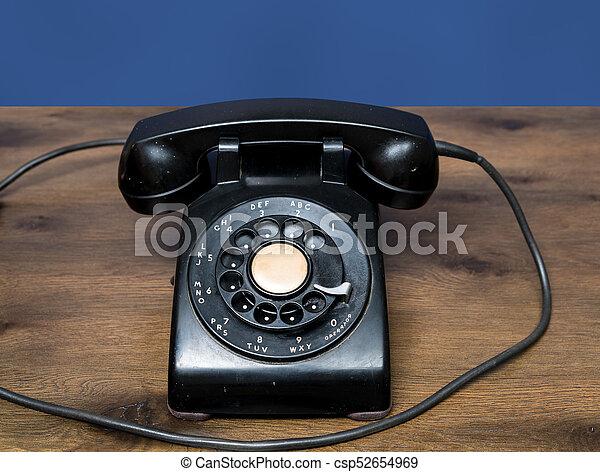 Un viejo teléfono de marca rotatorio antiguo en la mesa de madera - csp52654969