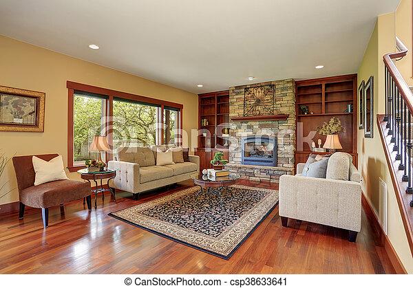 Cuarto familiar en estilo antiguo con chimenea de diseño de piedra natural y sofá viejo. - csp38633641