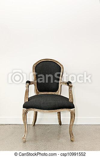 Un sillón antigüo cerca de la pared - csp10991552