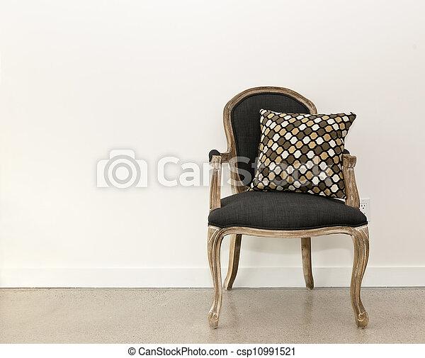 Un sillón antigüo cerca de la pared - csp10991521