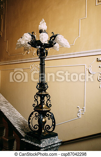 Antique antique lamp on the stair railings against the patterned wall. - csp87042298