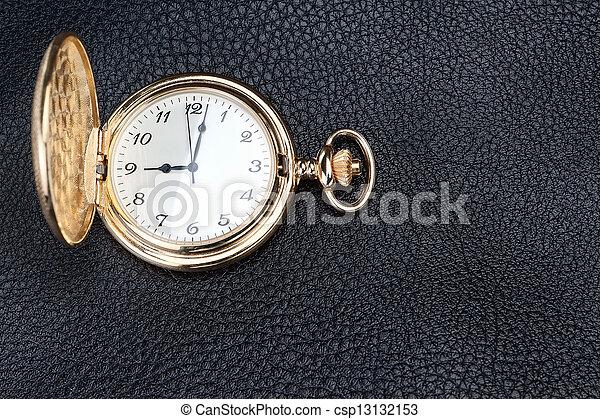 Antique gold pocket watch on a text - csp13132153