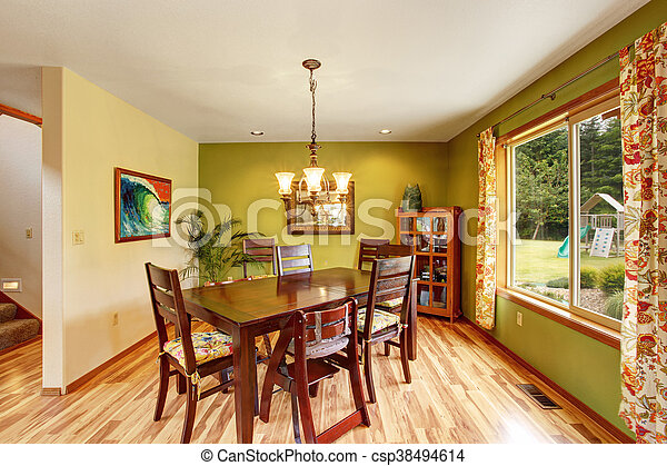 Antique green dining room interior with mahogany table set and chandelier. - csp38494614