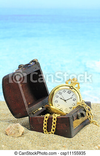 Antique pocket clock in a  treasure chest on a beach  - csp11155935