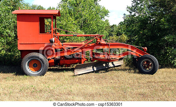antique road grader on a field with trees in the background
