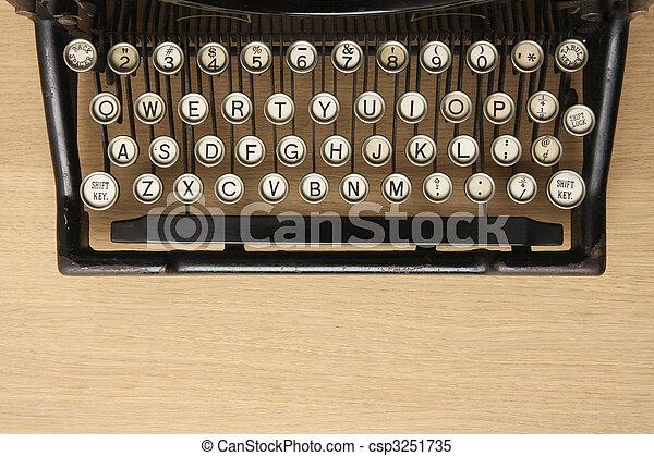 Antique typewriter on a wooden desk - csp3251735