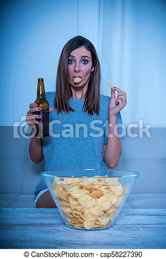 Anxious woman watching TV and eating - csp58227390