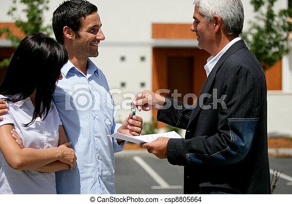 Una pareja recibiendo las llaves de su nuevo apartamento - csp8805664