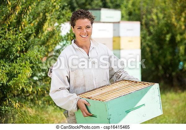 Mujer apicultor cargando una caja de panal - csp16415465