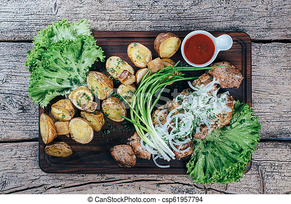 Appetizing roasted pork pieces on the grill, presented on a wooden board, along with leaves of green salad and potatoes with tomato sauce - csp61957794