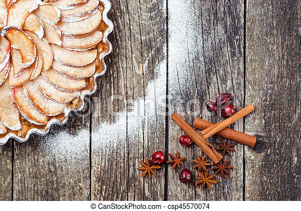 Apple pie tart on rustic wooden background. Ingredients - apples and cinnamon .Top view. - csp45570074