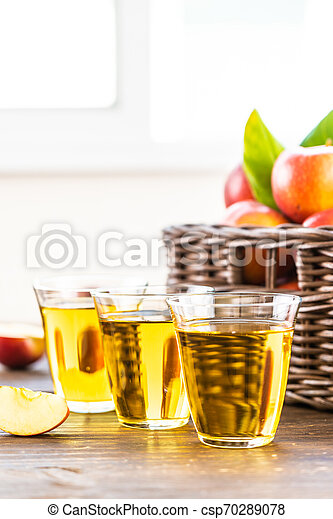 Apples juice in glass with apple in the basket - csp70289078