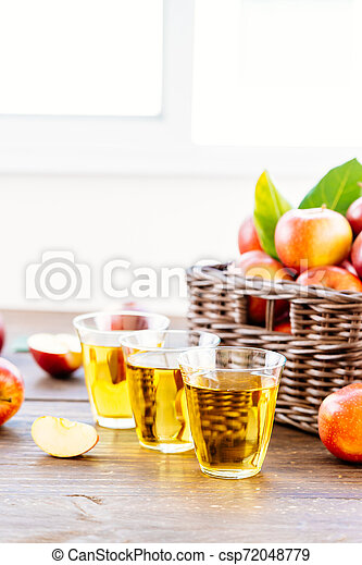 Apples juice in glass with apple in the basket - csp72048779