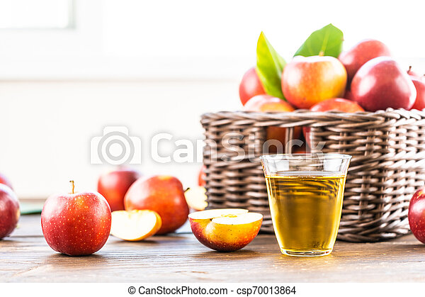 Apples juice in glass with apple in the basket - csp70013864