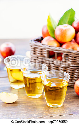 Apples juice in glass with apple in the basket - csp70389550