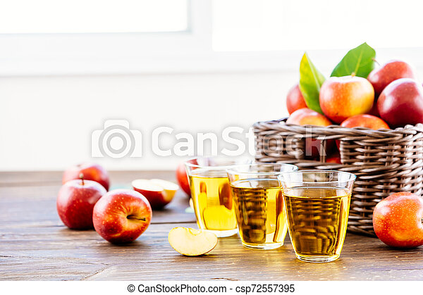 Apples juice in glass with apple in the basket - csp72557395