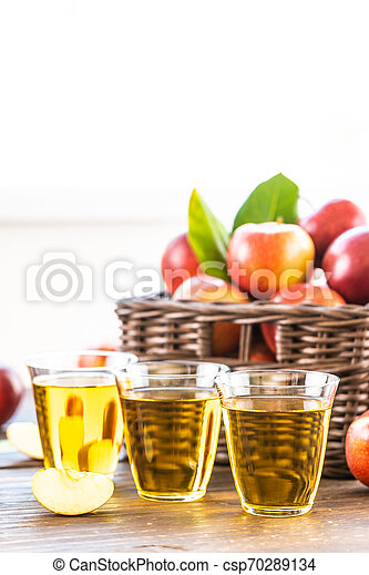 Apples juice in glass with apple in the basket - csp70289134