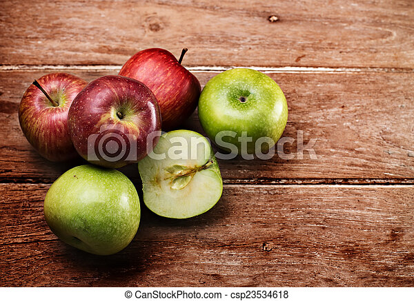 Apples on wooden background - csp23534618