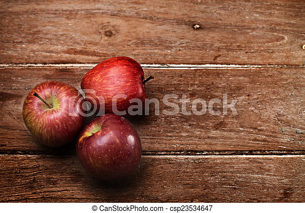 Apples on wooden background - csp23534647