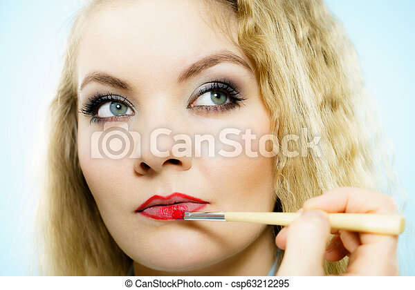 Applying lipstick on fashion model lips - csp63212295