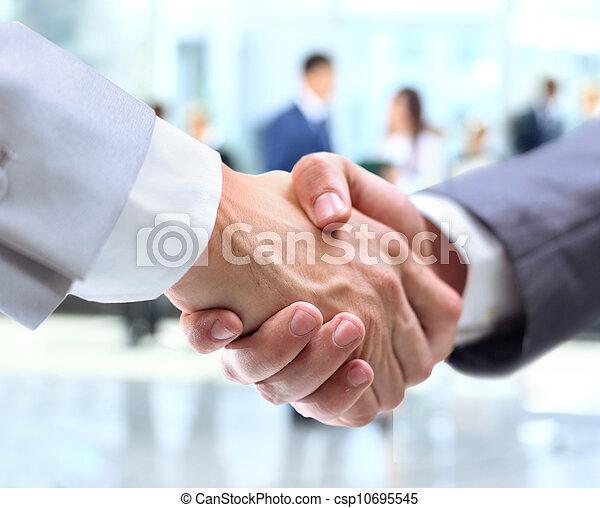 Un apretón de manos y gente de negocios - csp10695545