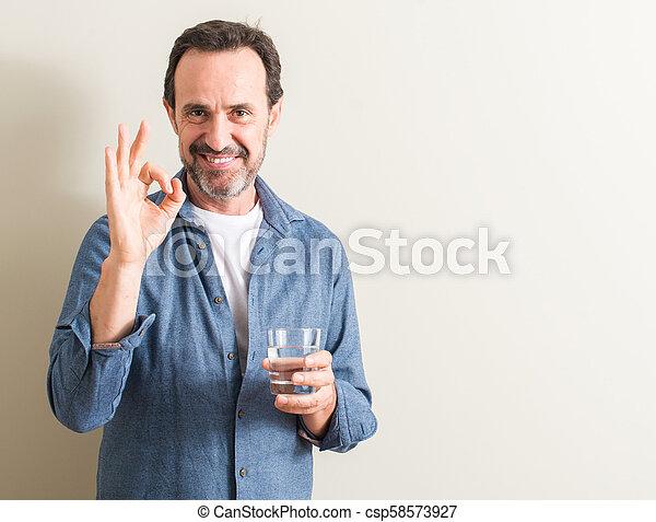 Señor bebiendo agua en un vaso haciendo bien signo con dedos, excelente símbolo - csp58573927