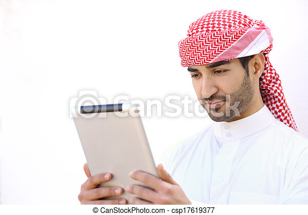 Arab man reading a tablet outdoor on white - csp17619377
