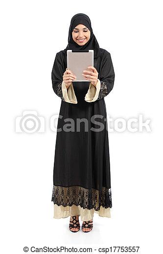 Arab saudi woman standing looking a tablet reader - csp17753557