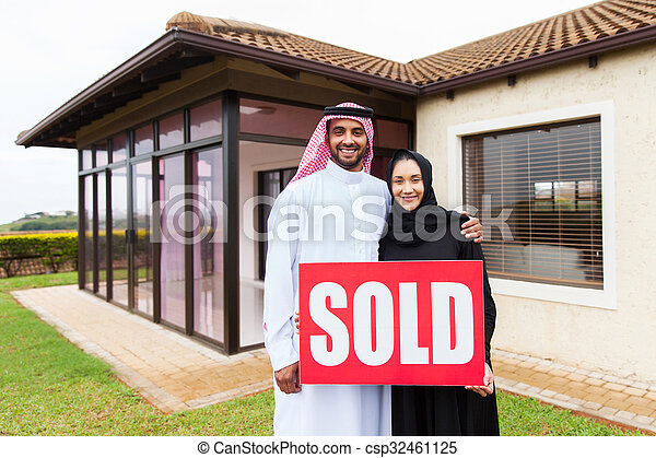 arabian couple with sold real estate sign - csp32461125