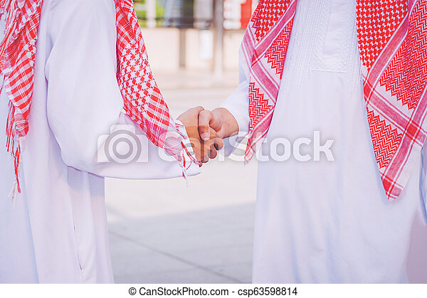 Arabic businessman giving an handshake to his business partner, on construction site - csp63598814